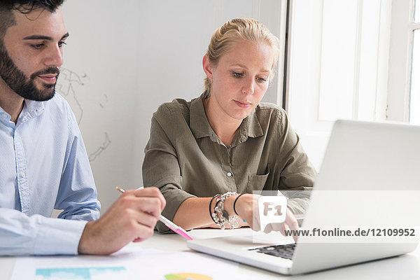 Junge Geschäftsfrau und Mann tippen am Laptop bei einer Bürobesprechung