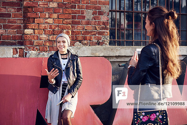 Two young female friends talking on city street