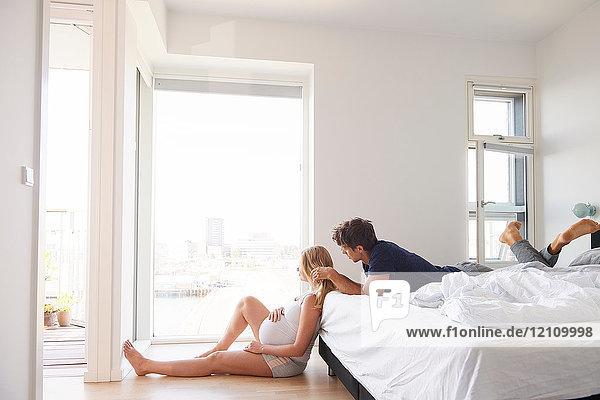 Auf dem Bett liegender Mann mit Hand auf dem Haar der schwangeren Freundin