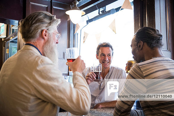 Drei reife Männer  die zusammen in der Kneipe sitzen und sich unterhalten