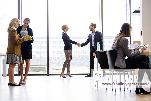 Geschäftsfrau und Mann schütteln sich am Bürofenster die Hand