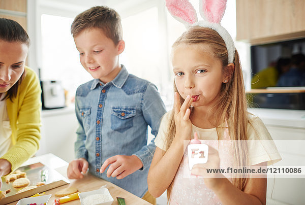 Girl licking her fingers while preparing easter biscuits on kitchen counter