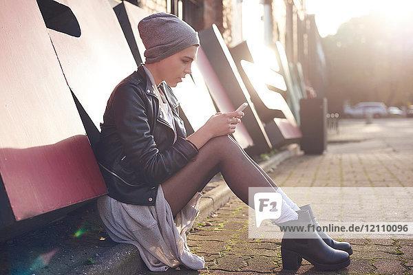Coole junge Frau sitzt auf der Straße in der Stadt und schaut sich ein Smartphone an