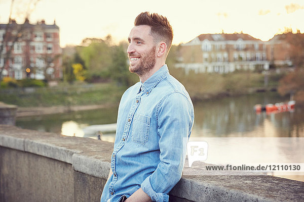 Bearded young man leaning against bridge over River Thames  Richmond  UK