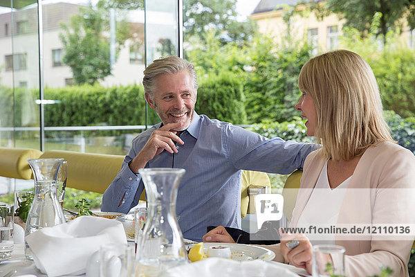 Lächelndes Paar beim Essen im Freien im Restaurant