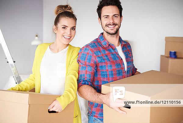 Junges Paar zieht nach Hause  hält Kartons in der Hand und lächelt