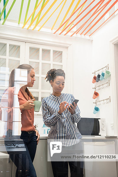 Two businesswomen looking at smartphone while taking a coffee break in office kitchen