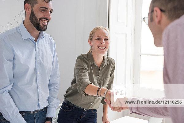 Geschäftsfrau und Mann schütteln sich am Konferenztisch die Hand