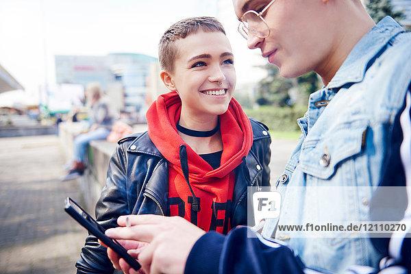 Junges Paar betrachtet Smartphone in der Stadt