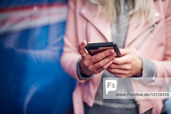 Mittlerer Abschnitt einer jungen Frau  die ein Smartphone an der Straßenbahnhaltestelle in der Hand hält