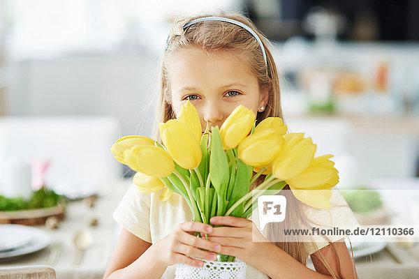 Porträt eines Mädchens  das sich hinter gelben Tulpen hält und versteckt