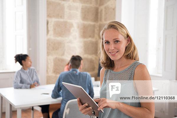 Porträt einer jungen Geschäftsfrau  die ein digitales Tablet im Büro hält