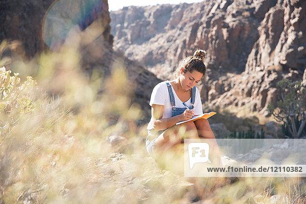 Junge Wanderin schreibt Notizen im Tal  Las Palmas  Kanarische Inseln  Spanien