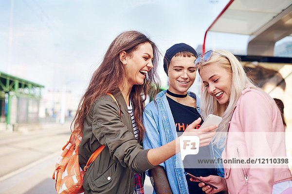 Three young female friends looking at smartphone at city tram station