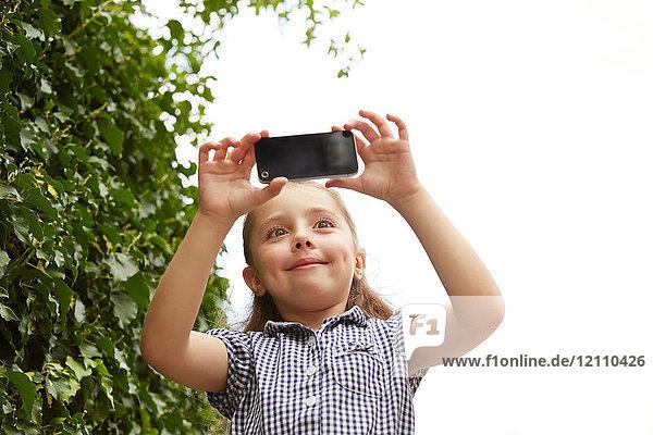 Junges Mädchen,  im Freien,  Fotografieren mit Smartphone,  Blick aus niedrigem Winkel