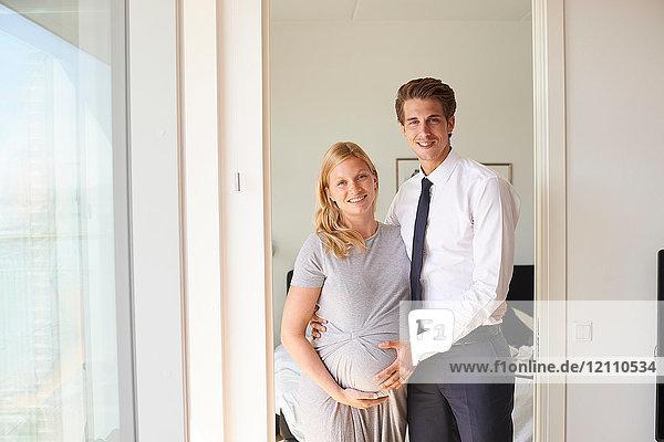 Porträt eines schwangeren Paares mit Händen auf dem Bauch in der Wohnung