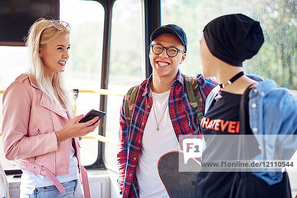 Three young adult friends chatting on city tram