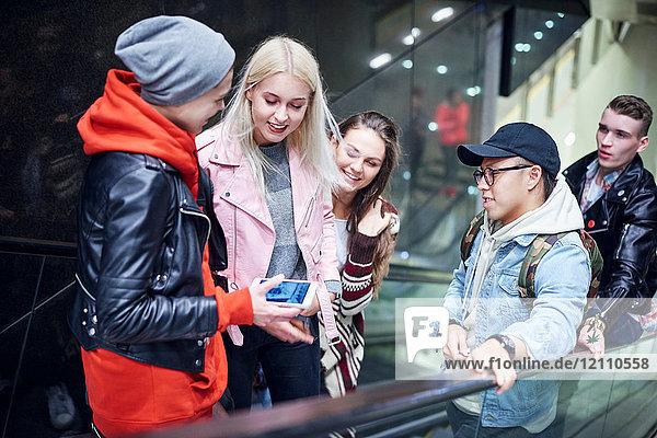 Junge erwachsene Freunde  die die Rolltreppe in der U-Bahn-Station hinauffahren und auf ein Smartphone schauen