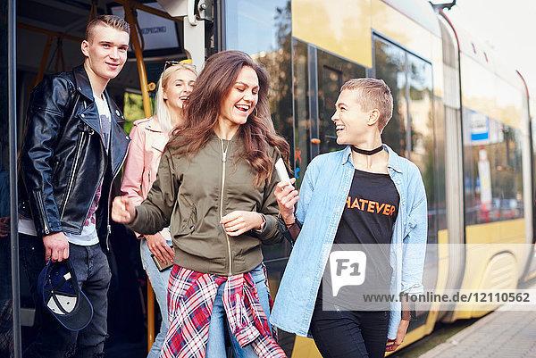Vier junge erwachsene Freunde steigen aus der Stadtbahn aus