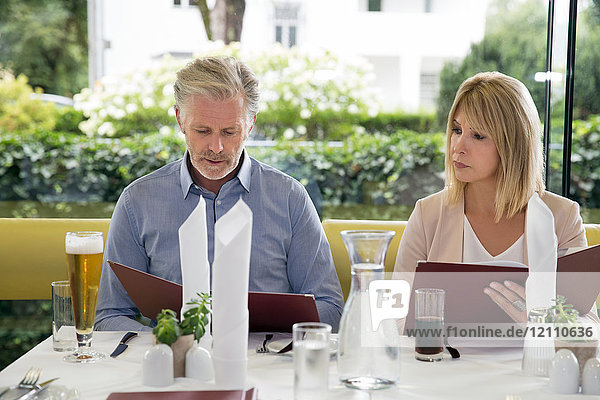 Couple al fresco dining at restaurant  selecting from menu