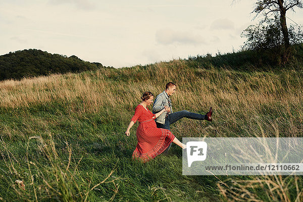 Fun pregnant couple marching in field