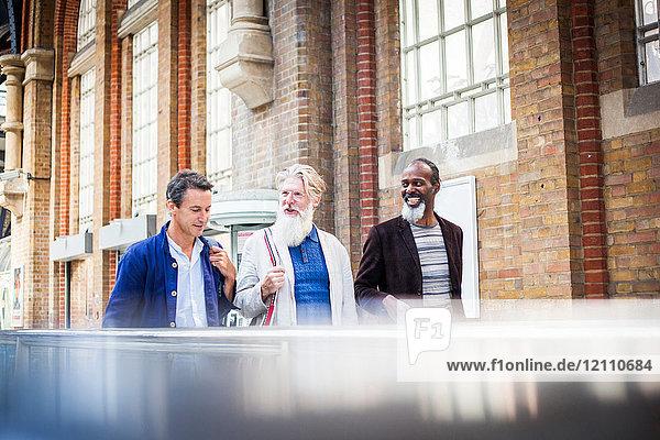 Drei reife Männer am Bahnhof  die zusammen gehen