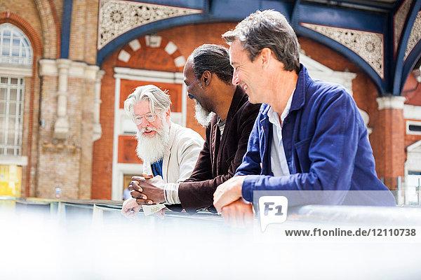 Drei reife Männer am Bahnhof  stehen zusammen und unterhalten sich