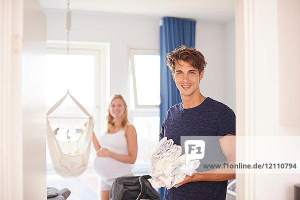 Porträt eines schwangeren Paares mit einem Stapel Babykleidung im Kinderzimmer