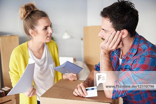 Junges Ehepaar zu Hause  umgeben von Pappkartons  erarbeitet Finanzen
