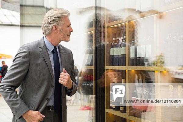 Man window shopping in wine shop window