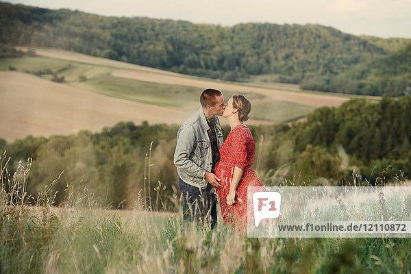 Romantisches schwangeres Paar im mittleren Erwachsenenalter küsst sich auf dem Feld