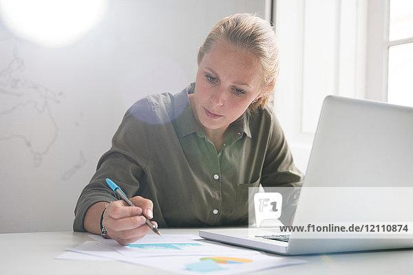 Junge Geschäftsfrau macht Notizen und benutzt Laptop am Bürotisch