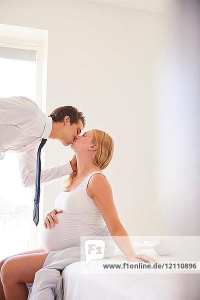Schwangere Frau küsst Geschäftsmann-Ehemann im Schlafzimmer