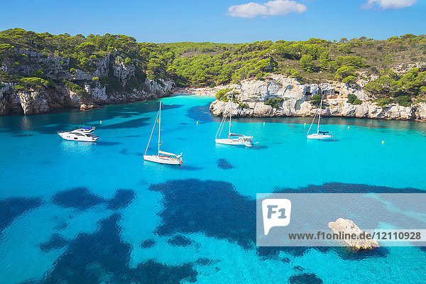 View of Cala Macarelleta bay with blue sea and anchored yachts  Menorca  Balearic Islands  Spain