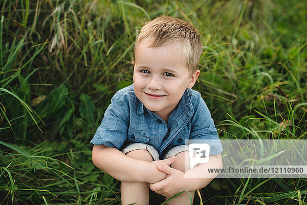 Portrait of smiling boy sitting in tall grass looking at camera