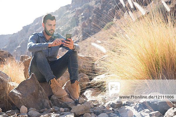Junger männlicher Wanderer sitzt auf einem Felsblock und schaut auf ein Smartphone im Tal  Las Palmas  Kanarische Inseln  Spanien