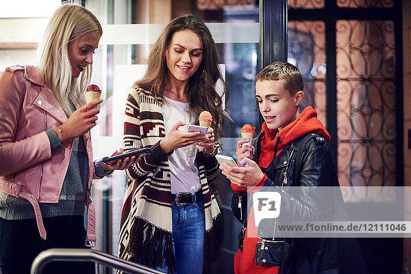 Drei junge Frauen mit Eistüten  die auf der Straße in der Stadt Smartphones anschauen