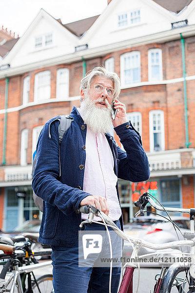 Ein erwachsener Mann steht neben dem Fahrrad und benutzt ein Smartphone