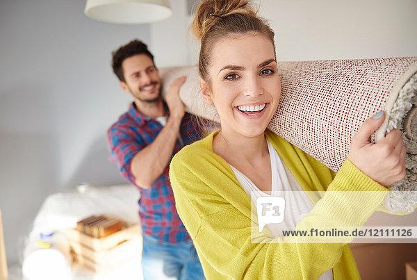 Junges Paar zieht nach Hause  trägt einen gerollten Schlepper auf den Schultern und lächelt