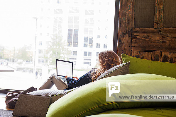 Rückansicht einer Frau,  die mit einem Laptop auf einem Sofa sitzt