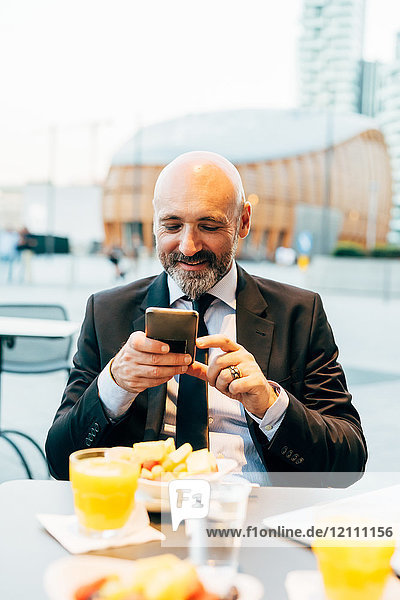Mature businessman sitting outdoors at cafe  using smartphone