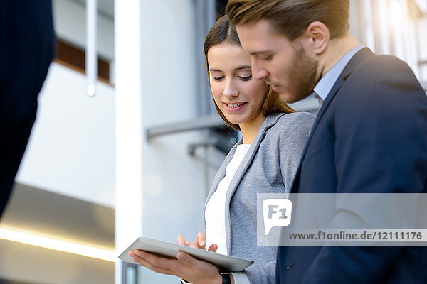 Junge Geschäftsfrau und Mann benutzen digitalen Tablet-Touchscreen im Atrium des Büros