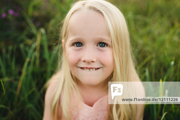 Portrait of blonde haired girl looking at camera smiling