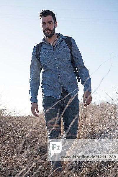 Junger männlicher Wanderer wandert durch langes Gras  Las Palmas  Kanarische Inseln  Spanien