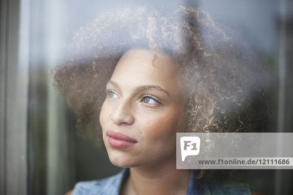 Nahaufnahme einer nachdenklichen Frau mit lockigem Haar durch ein Glasfenster gesehen