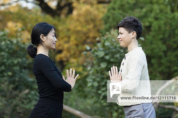 Seitenansicht von Frauen mit umklammerten Händen beim Yoga gegen Bäume im Park