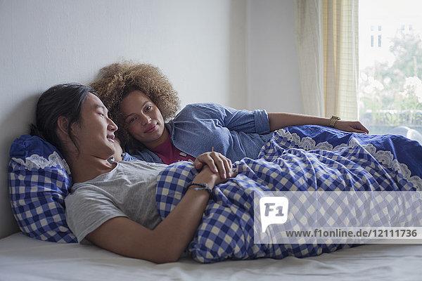 Junges Paar auf dem Bett liegend an der weißen Wand am Fenster zu Hause