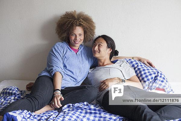 Lächelndes junges Paar ruht auf dem Bett gegen die weiße Wand zu Hause.