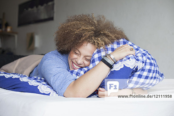 Happy woman with closed eyes holding pillow while lying on bed at home