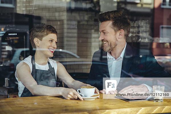 Kellnerin serviert Kaffee für lächelnde Kunden im Cafe